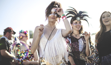 Two smiling young women at a summer music festival face painted, wearing feather headdress, standing among the crowd, looking at camera. - MINF05558