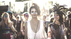 Two smiling young women at a summer music festival face painted, wearing feather headdress, standing among the crowd, looking at camera. - MINF05561