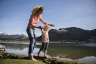 Austria, Tyrol, Walchsee, happy mother and daughter walking at the lake - JLOF00149