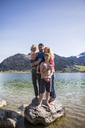 Austria, Tyrol, Walchsee, happy family standing on boulder in the lake - JLOF00152