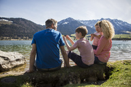 Austria, Tyrol, Walchsee, happy family sitting at the lakeside - JLOF00155