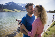 Austria, Tyrol, Walchsee, happy couple embracing at the lake with family in background - JLOF00158