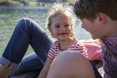 Austria, Tyrol, Walchsee, happy brother and sister smiling at each other at the lakeside - JLOF00164