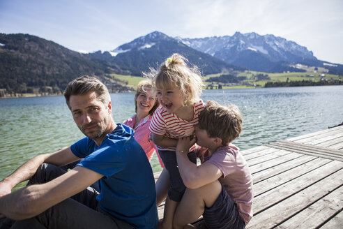 Austria, Tyrol, Walchsee, happy family sitting on a jetty at the lakeside - JLOF00170