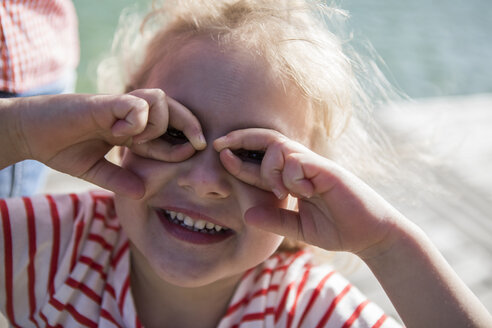 Portrait of happy girl making finger glasses - JLOF00173