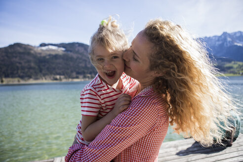 Austria, Tyrol, Walchsee, happy mother carrying daughter at the lake - JLOF00176