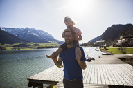 Austria, Tyrol, Walchsee, happy father carrying daughter on shoulders at the lake - JLOF00185