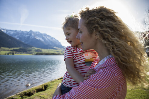Austria, Tyrol, Walchsee, happy mother carrying daughter at the lake - JLOF00191