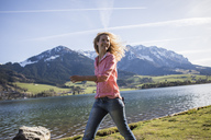 Austria, Tyrol, Walchsee, smiling woman walking at the lake - JLOF00194
