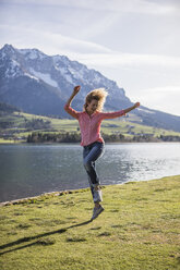 Austria, Tyrol, Walchsee, happy woman jumping at the lake - JLOF00197