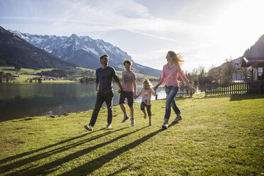 Austria, Tyrol, Walchsee, happy family walking at the lakeside - JLOF00200