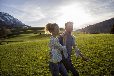 Austria, Tyrol, Walchsee, happy couple hiking on an alpine meadow - JLOF00203
