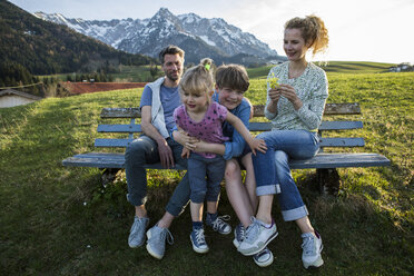 Austria, Tyrol, Walchsee, happy family resting on a bench in the mountains - JLOF00206