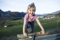 Austria, Tyrol, Walchsee, happy girl on a bench - JLOF00212