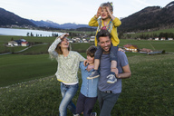 Austria, Tyrol, Walchsee, happy family hiking on an alpine meadow - JLOF00215