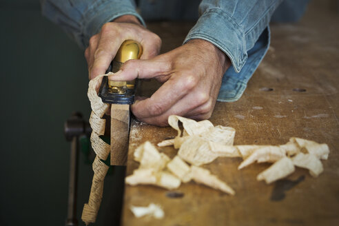A craftsman holding a spokeshave and using it to shape a piece of wood in a clamp. - MINF05903