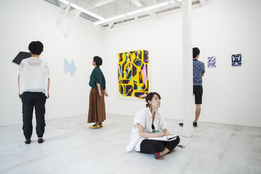Woman with black hair sitting on floor in art gallery with pen and paper, looking at modern painting, three people standing in front of artworks. - MINF05975