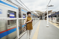 Woman wearing sunglasses standing on the platform of a subway station, Tokyo commuter. - MINF05993