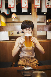 Woman sitting at a table in a restaurant, drinking from large glass of beer. - MINF05999