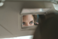 Woman mirrored in rear view mirror applying mascara in car - AFVF01280