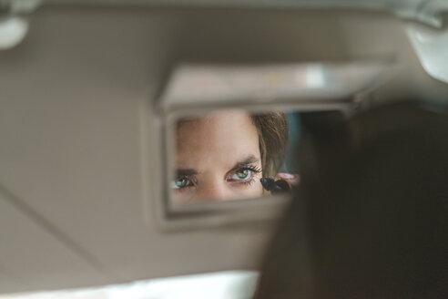 Woman mirrored in rear view mirror applying mascara in car - AFVF01280