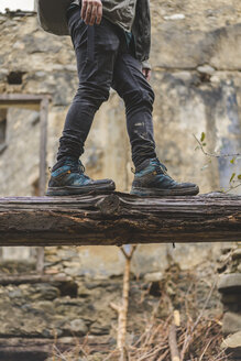 Man balancing on dead wood, partial view - AFVF01286