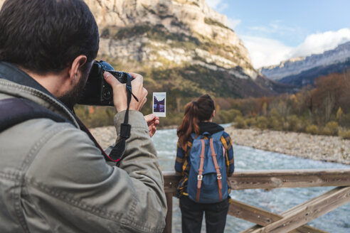 Spain, Ordesa y Monte Perdido National Park, man taking picture of woman and instant photo - AFVF01292