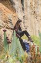 Spain, Alquezar, young woman sitting on a rock using smartphone - AFVF01307