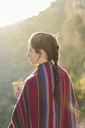 Spain, Alquezar, woman with braid and coffee mug at backlight - AFVF01310
