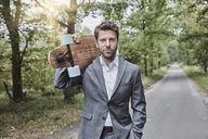 Portrait of businessman carrying skateboard on rural road - RORF01362