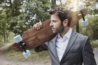 Portrait of businessman carrying skateboard on rural road - RORF01365