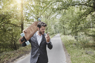 Angry businessman with skateboard shouting at smartphone on rural road - RORF01371