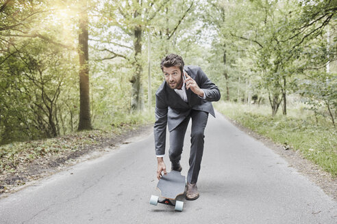 Businessman walking with skateboard and smartphone on rural road - RORF01374