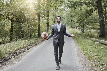 Happy businessman walking with basketball on rural road - RORF01377