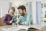 Father and daughter using microscope at home - RORF01389