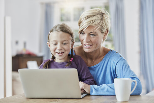 Mother and daughter using laptop at home - RORF01392