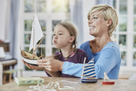 Happy mother and daughter playing with model boat at home - RORF01395