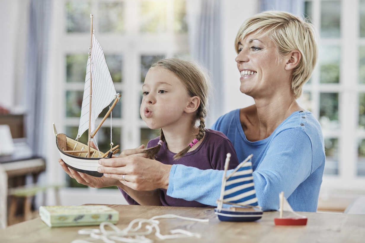 Happy mother and daughter playing with model boat at home - RORF01395 - Roger Richter/Westend61