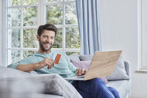 Portrait of smiling man at home shopping online - RORF01398