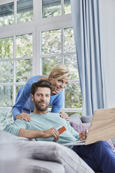 Portrait of couple at home shopping online - RORF01401