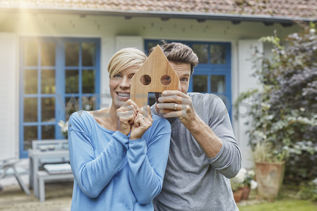 Portrait of smiling couple standing in front of their home holding house model - RORF01407 - Roger Richter/Westend61