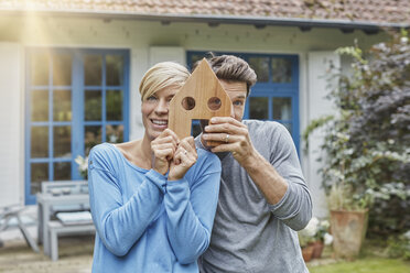 Portrait of smiling couple standing in front of their home holding house model - RORF01407