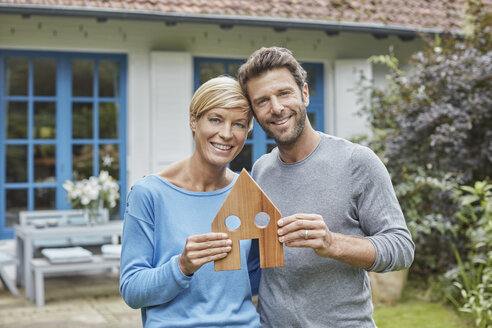 Portrait of smiling couple standing in front of their home holding house model - RORF01410