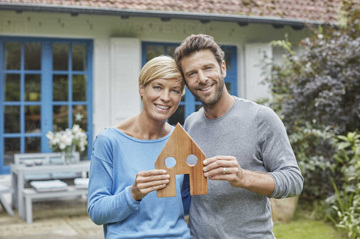 Portrait of smiling couple standing in front of their home holding house model - RORF01410 - Roger Richter/Westend61