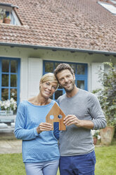 Portrait of smiling couple standing in front of their home holding house model - RORF01413
