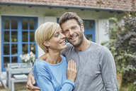 Portrait of smiling couple standing in front of their home - RORF01416