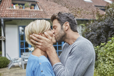 Couple kissing in front of their home - RORF01419