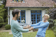 Happy couple dancing in front of their home - RORF01422