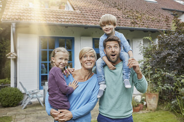 Portrait of happy family with two kids in front of their home - RORF01428