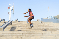 Young woman during workout on stairs, jumping - AFVF01323